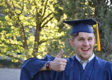 Graduate in cap and gown giving the thumbs up sign